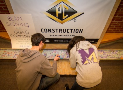 "PC Construction is building the Quad Commons project, consisting of a 40,000 sq-ft multifunctional student center and a 43,000-sq-ft. residence hall, at Saint Michael's College. PC Construction and the College hosted a ""beam-signing"" event, with hundreds of students signing a 16-ft construction beam that will serve as a time vault in the new student center which is scheduled for completion this summer on the Colchester, Vt. campus. Photo courtesy of Saint Michael's College."