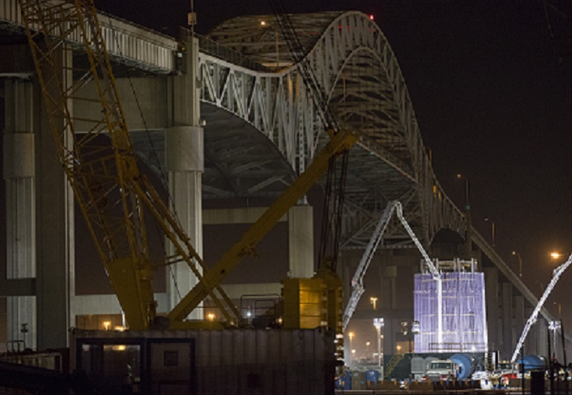 The first segment of a tower for the new bridge at the Port of Long Beach is aglow during a pile cap pour. The existing Gerald Desmond Bridge, in the background, will be demolished once the new bridge is complete. Photo courtesy of Port of Long Beach/Jonathan Alcorn