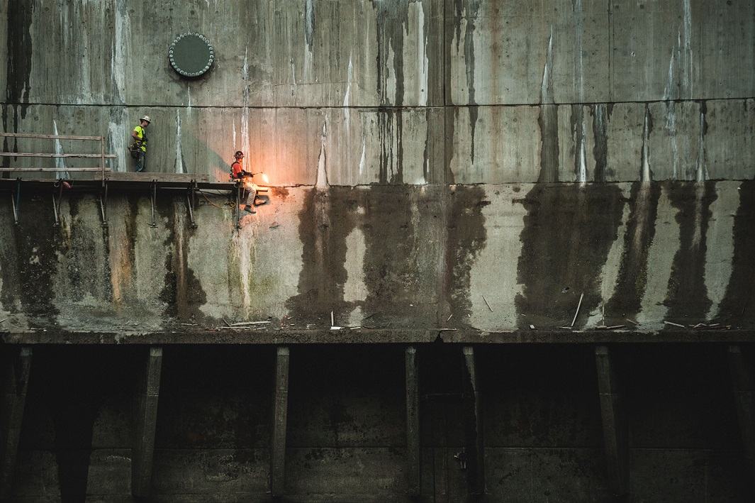 Dismantling the scaffolding walkway on top of the old spillway and beneath the new dam as the project wraps up.